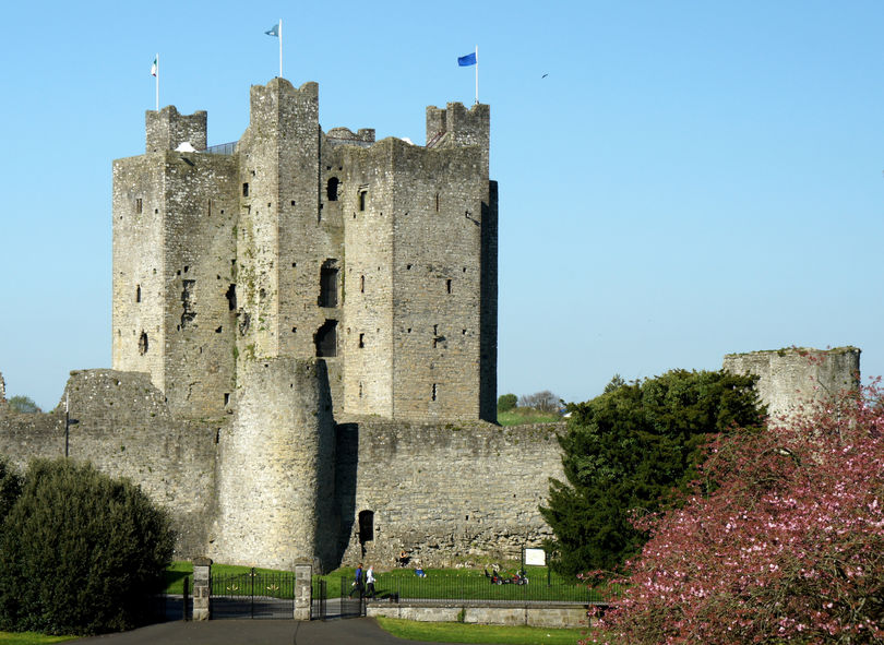 The tall keep of Trim Castle, Ireland, is largely intact. Flags fly from the towers. Blue sky.